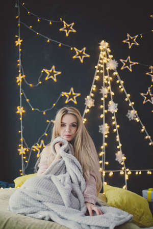 young woman in a plaid posing against the background of Christmas garlands.
