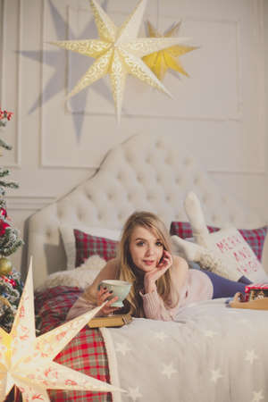 young woman sitting with tea mug in christmas interior. enjoy the holiday