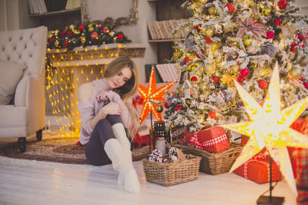 Beautiful young woman in a Christmas interior. Dressing a Christmas tree. Imagens