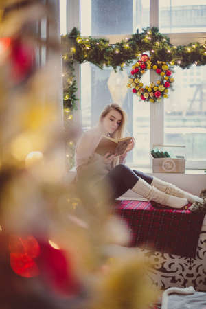 young blond woman in leggings sitting on the window. to read a book. christmas interior Imagens