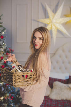 Beautiful young woman in christmas interior.Box with Christmas toys