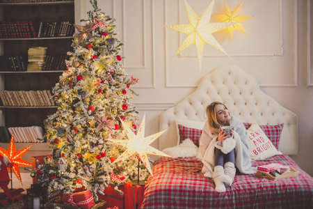 young woman in christmas interior. Sit with a plaid and a cup of tea. Imagens