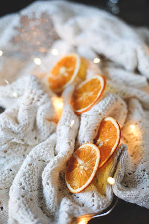 dried orange slices, christmas decor. white plaid with a garland. close-up Imagens