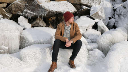 young male fisherman sitting on the ice Imagens