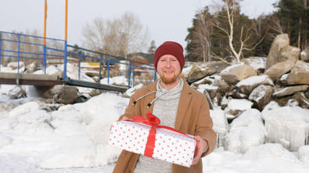 young man gives a gift on the background of snow and ice