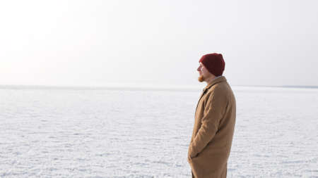 a young man walks on the ice in winter