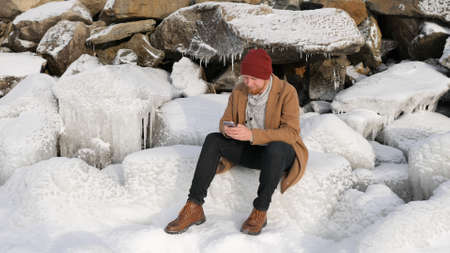 man sitting on the ice and talking on the phone