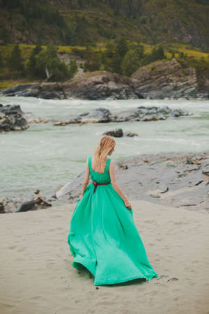 young woman in a long flowing dress on the background of the river and mountains. coloring women goes in a green dress on a background of a beautiful landscape. a woman walks beside a river. soft light.