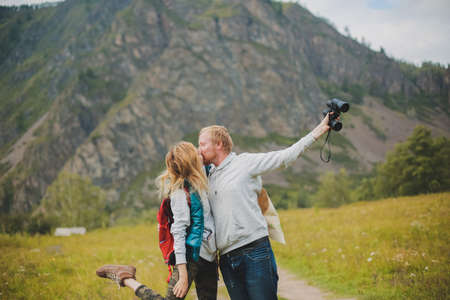 couple in love travels in the mountains with a map and binoculars. friends travelers are looking for directions on the map. man and woman tourists in the mountains. jump and rejoice that they have found the way.couple of travelers with a map rejoice among the mountains Imagens