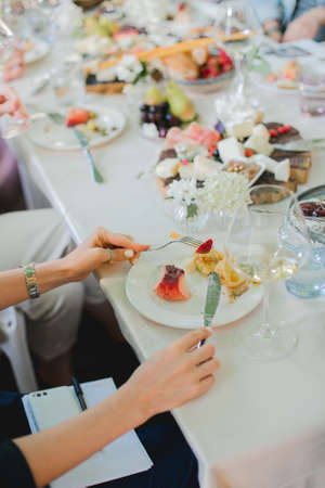 Wedding table setting. Festive table with white tablecloth. guests sit at the table. on the table are fruits, cheeses, glasses. cheese and wine tasting
