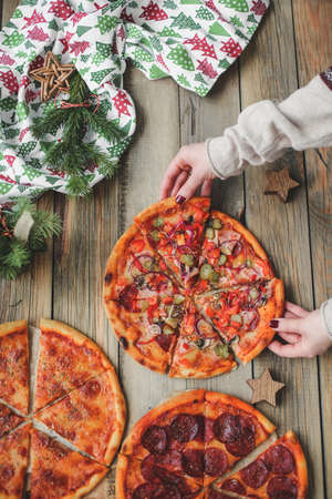 Three pizzas lie on a wooden table against the background of Christmas decor. top view of three pizzas to which hands reach.