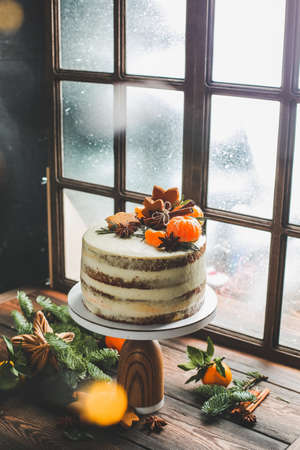 Christmas cake on a window background. Christmas cake stands by the window, which is snowing. Imagens - 137048002