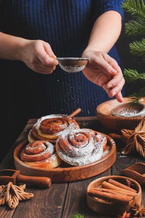 Homemade fresh cinnamon roll. Christmas cinnamon roll. pour flour or icing sugar on buns. Imagens