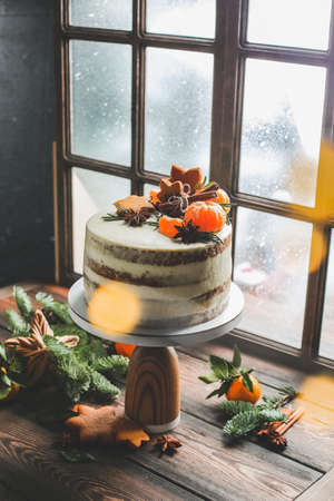 Christmas cake on a window background. Christmas cake stands by the window, which is snowing.