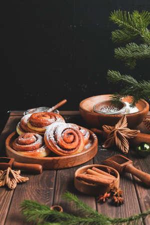 Homemade fresh cinnamon roll. Christmas cinnamon roll. Homemade traditional winter holiday dessert cookies on dark wooden background.