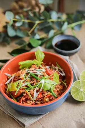 Bowl of stir fried udon noodles garnished with black sesame seeds and fresh mint with green chopsticks.