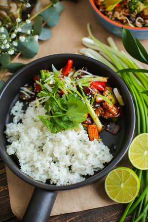 Bowl of stir fried udon noodles garnished with black sesame seeds and fresh mint with green chopsticks