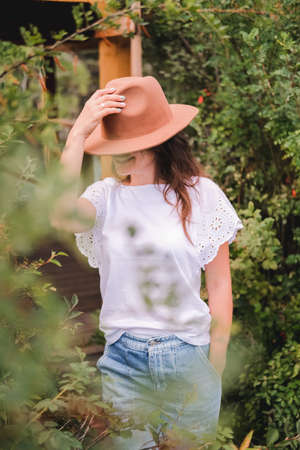 Attractive brunette in a hat and white shirt is enjoying nature in the mountains. Beautiful young woman in a shirt and jeans walks along the beautiful landscape Imagens