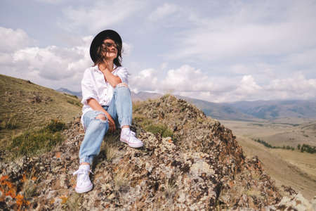 Attractive brunette in a hat and white shirt is enjoying nature in the mountains. Beautiful young woman in a shirt and jeans walks along the beautiful landscape.