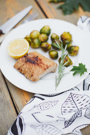 Fish baked with cheese and tomatoes, Brussels sprouts and cherry tomatoes, delicious dish, healthy food Imagens - 158495359