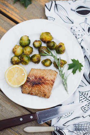 Fish baked with cheese and tomatoes, Brussels sprouts and cherry tomatoes, delicious dish, healthy food Imagens