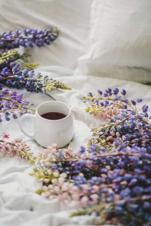 spring composition with flowers and a cup of tea on a white sheet. flowers and a cup of coffee among the flowers. Flat lay, top view Imagens - 158495793