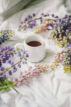 spring composition with flowers and a cup of tea on a white sheet. flowers and a cup of coffee among the flowers. Flat lay, top view Imagens - 158567307