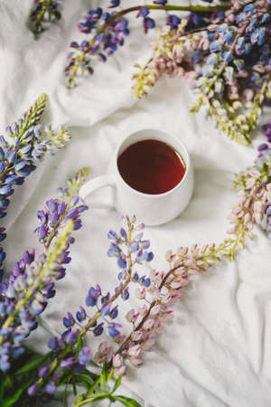 spring composition with flowers and a cup of tea on a white sheet. flowers and a cup of coffee among the flowers. Flat lay, top view Imagens - 158567722