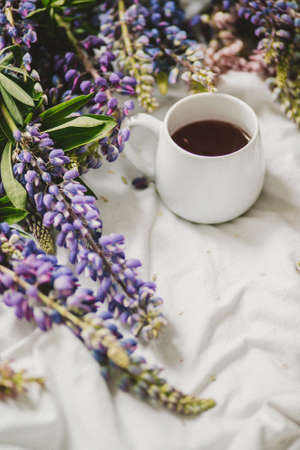 spring composition with flowers and a cup of tea on a white sheet. flowers and a cup of coffee among the flowers. Flat lay, top view Imagens - 158567727