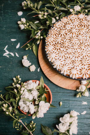 beautiful pie with white meringue cream on a wooden background among white flowers. Viewpoint from above.