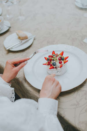 Photo of female hands cutting a fruit cake with strawberries, mint and black currants on a white plate on a table in a restaurant. dessert pavlova. table etiquette Imagens