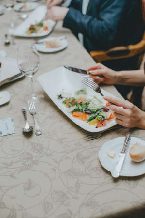 There is a salad close-up. hands properly hold cutlery in the restaurant. table etiquette. Imagens