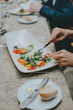 There is a salad close-up. hands properly hold cutlery in the restaurant. table etiquette