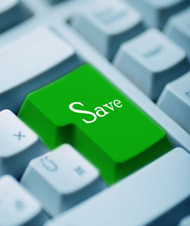 A green button reading SAVE on a computer keyboard