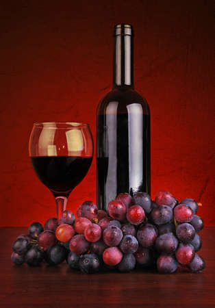 Bottle and glass of red wine with grapes against red backround