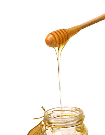 Honey with wooden drizzler on white background photo