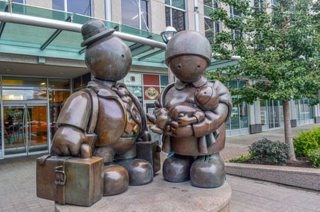immigrant: TORONTO,CANADA-AUGUST 15,2015: The bronze Immigrant Family sculpture by Tom Otterness on Yonge Street.