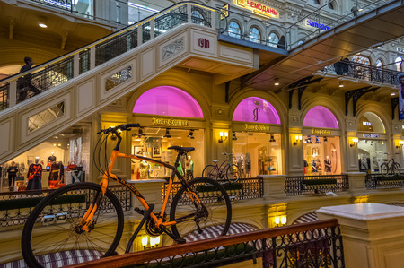 view of an atrium in a building: Moscow, Russia - April 10, 2015: View of the galleries the second and third floors in the State Department Store GUM with the orange bike.