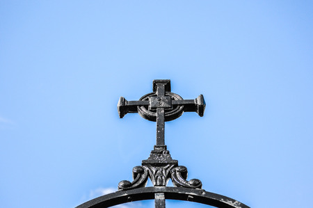 Iron fence with cross against blue sky in Montreal Stock Photo