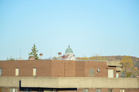 oratoria: St Joseph Oratory behind the roof of the residential building in fall in Montreal (Canada)