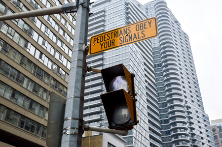 obey: Toronto, Canada - November 16, 2016: Traffic light in Toronto downtown, Canada. Pedestrians obey your signals.