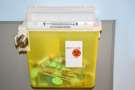 Foto van een afgesloten gele sharps container met gebruikte spuiten, naalden en een schaar.
