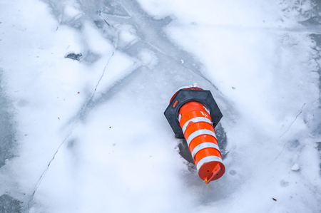 The orange traffic cone on the ice in Montreal downtown, Canada