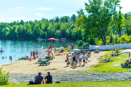 Saint-Adele, Canada - August 12, 2018: People relax on the lake beach in summer