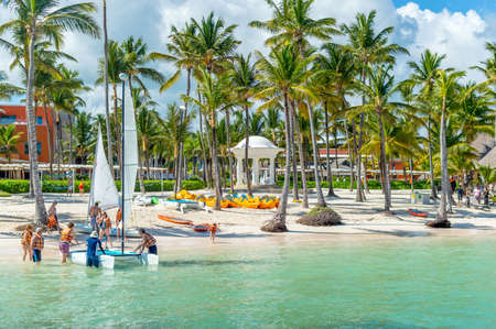 Punta Cana, Dominican Republic - October 26, 2018: People relax on the beach among palm trees in the resort of Punta Cana.