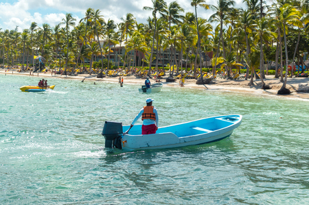 The rescue boat and the people relaxing on the beach among palm trees in the resort of Punta Cana. Publikacyjne