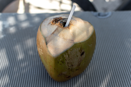 Fresh coconut with the straw inside of it.