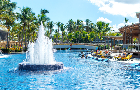 People relax in the swimming pool among palm trees in the resort of Punta Cana.
