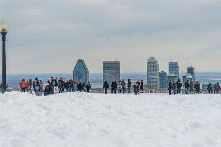 Montreal, Canada - February 16, 2020: Many tourists are standing on Kondiaronk Belvedere to enjoy Montreal skyline. Montreal Skyline in winter, Canada