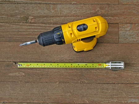 Two construction tools sitting on a wooden floor